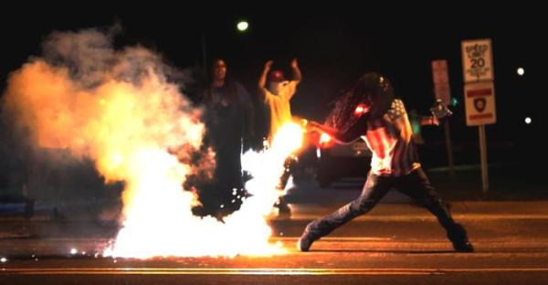 Brave young man in #Ferguson tosses a tear gas canister back toward the police officers who shot it at him.