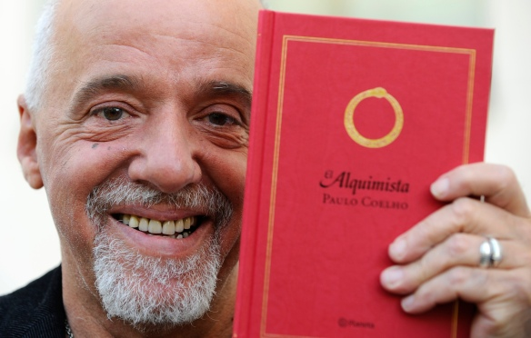 Brazilian writer Paulo Coelho holds a copy of his novel The Alchemist in Aviles, northern Spain