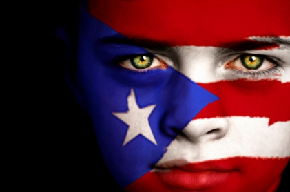 Portrait of a boy with the flag of Puerto Rico painted on his face.
