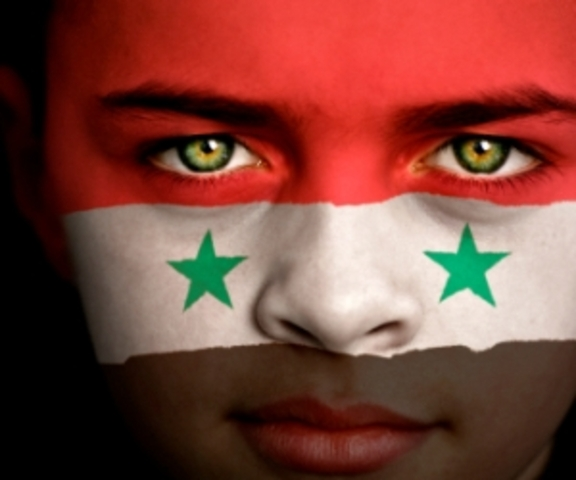 Portrait of a boy with the flag of Syria painted on his face